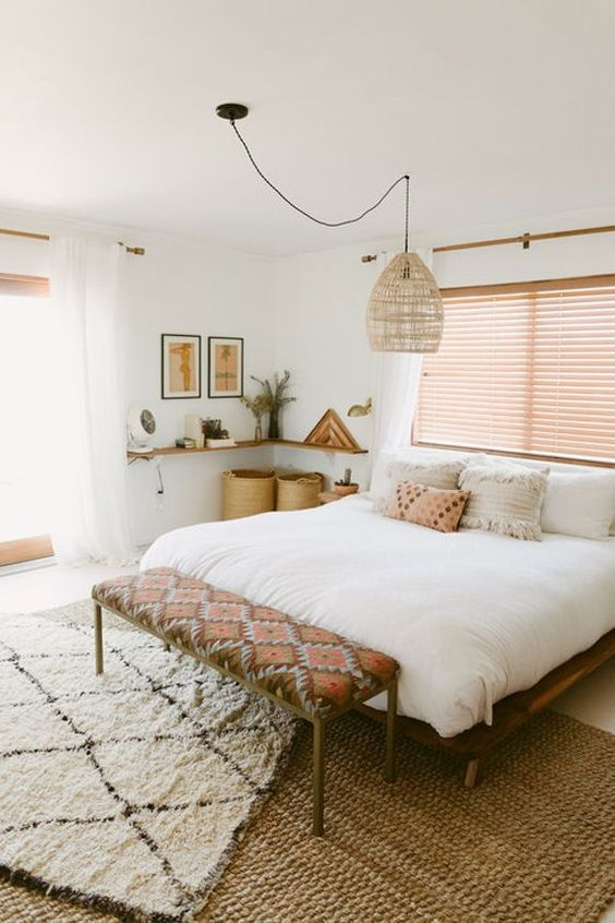 bedroom, beige floor, rattan rug, white fur rug, wooden bed platform, white bedding, shade, floating shelves, rattan covered pendant, geometric cushioned bench