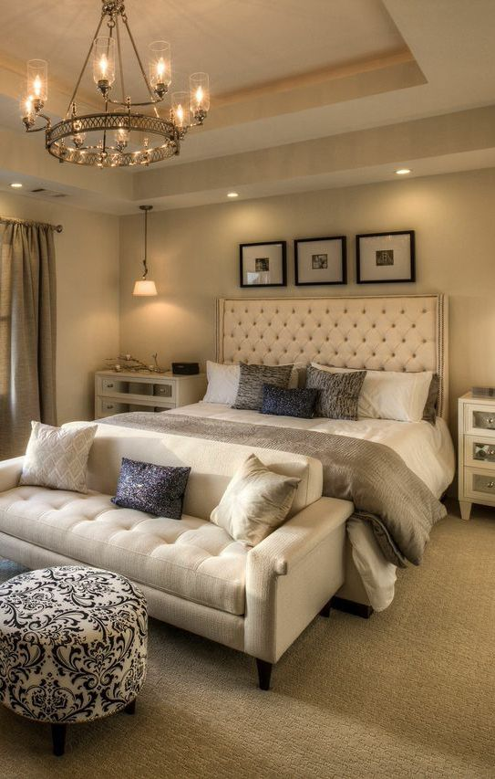 bedroom, beige rug flooring, white sofa, white blue ottoman, white bedding, white tufted headboard, off white wall and tray ceiling, pendant, bedside cabinet, chandelier