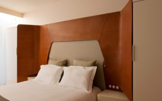 bedroom, beige wall, white bedding, wooden smooth designed wraparound headboar, built in cupboard