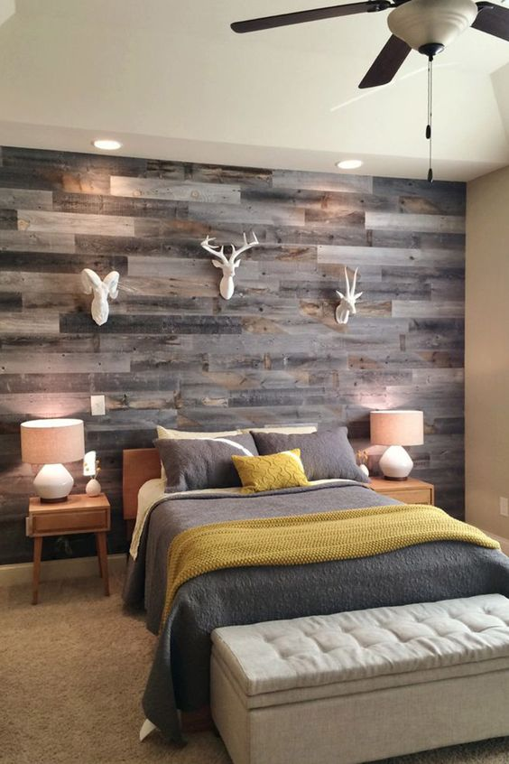bedroom, brown rug, grey bedding, grey wooden planks on the wall, white wall, wooden side table, table lamps, grey bench storage