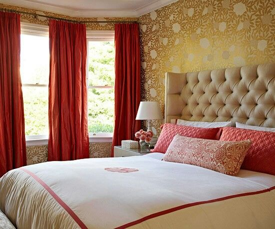 bedroom, golden wallpaper, brown wraparound tufted headboard, red pillows, bedside table, red curtain