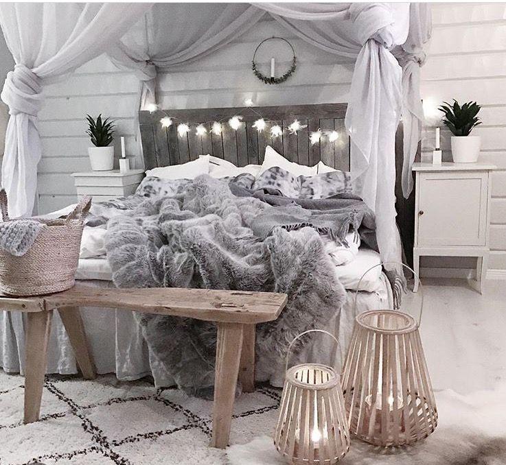 bedroom, grey floor, white rug, white wooden plants wall, wooden headboard, white beding, grey blanket, light grey curtain, wooden bench, rattan basket, wooden traditional light