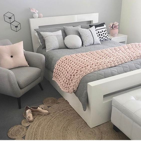 bedroom, grey flooring rug, rattan rug, grey chair, white bed platform, grey bedding, white bench, grey wall