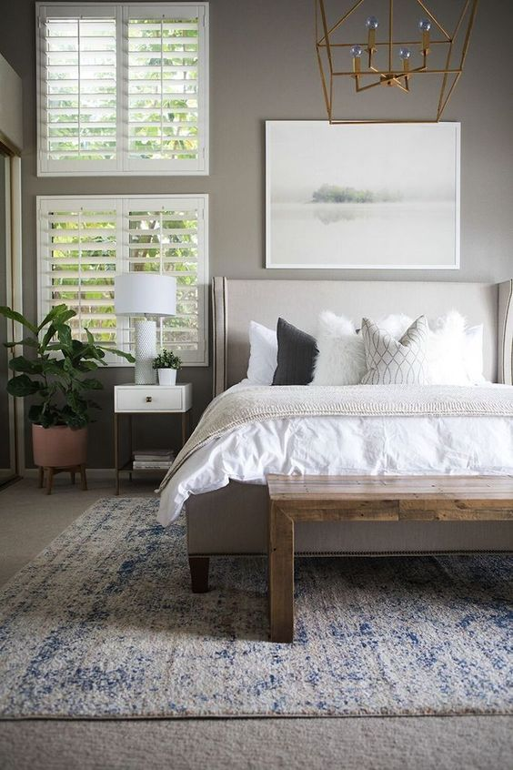bedroom, grey rug flooring, blue rug, white bedding, grey bed platform, grey wall, white bedside table, bed table lamp, plants on pot, geomteric chandelier
