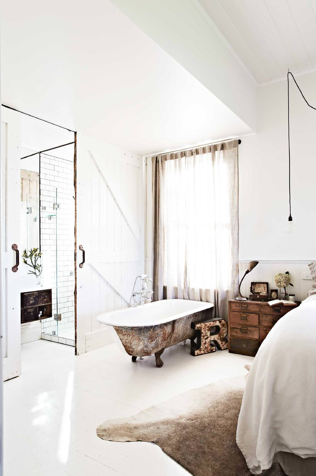 bedroom in white floor, white wall, white wooden door, wooden side cabinet, rusted look bathtub with clawfoot