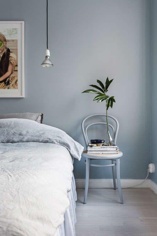 bedroom, light grayish blue wall, bedding, chair, wooden floor, pendant