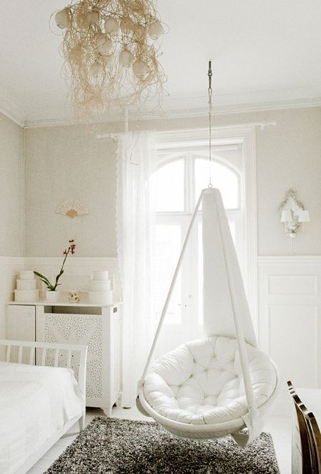 bedroom swing in white, white round seating, white cushion, white wall, white cedding, grey rug white ceiling. chandelier