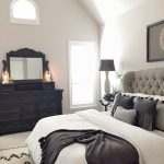 Bedroom, White Floor, White Rug, White Wall, White Ceiling, Black Wooden Cabinet With Mirror, Chandelier, White Bedding, Grey Turfted Wraparound Headboard, Side Table