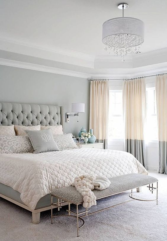 bedroom, white rug flooring, grey bench, light grey wall, white ceiling, white covered crystal chandelier, white bedding, grey tuffed bed platform, orange grey curtains
