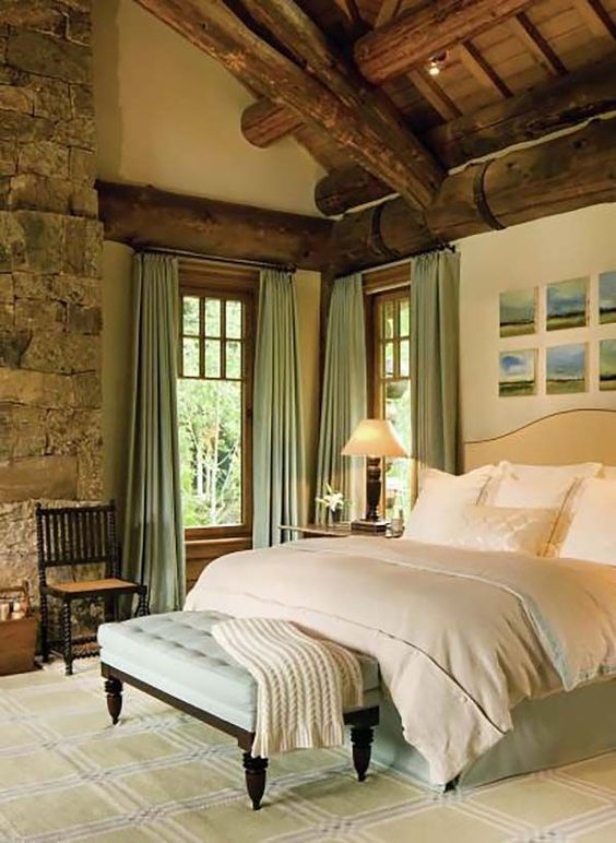 bedroom, white rug, wooden bench white tufted seating, white bedding, beige wall, stone open wall, wooden beams on the ceiling, windows