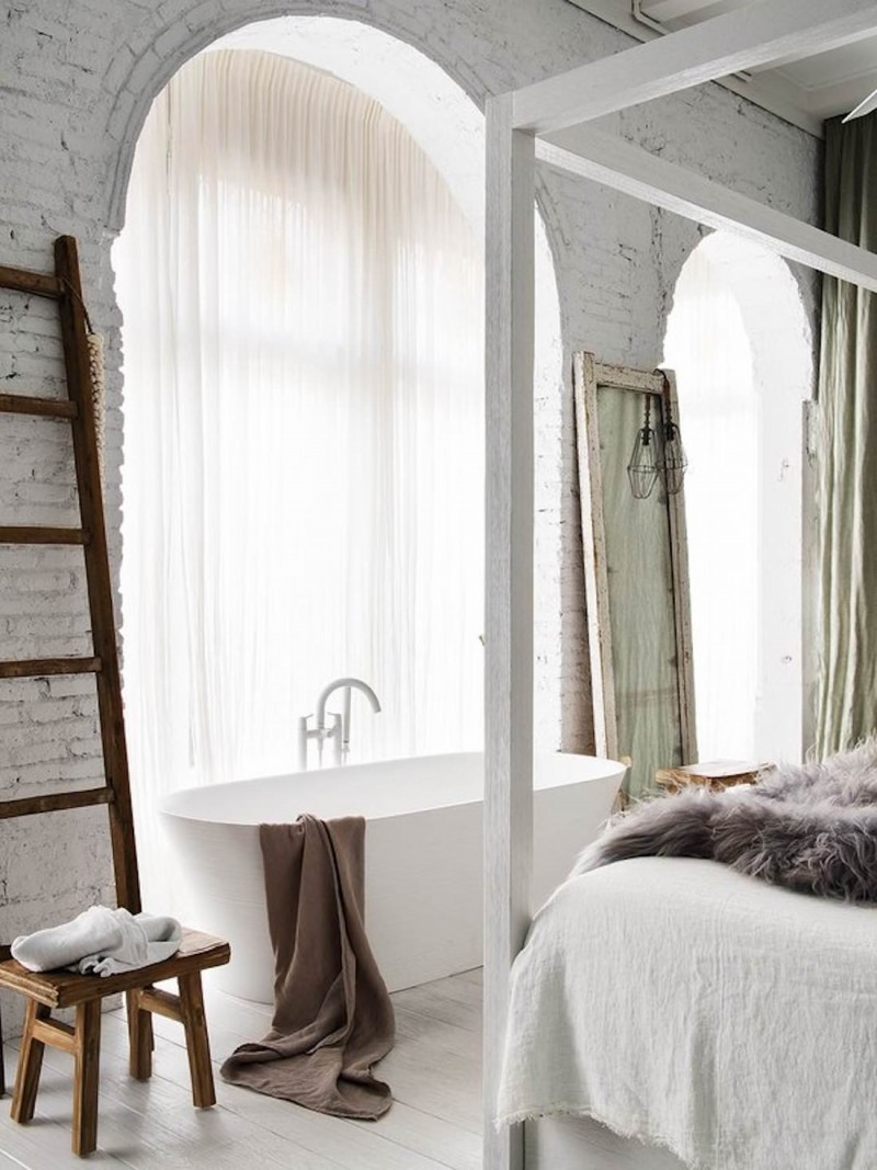 bedroom, white wooden floor, white bed platform with canopy support, white bedding, white open brick wall, white tub, wooden rack
