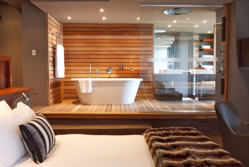 bedroom with wooden floor, opened bathroom with wooden slats in floor and wall, clear divider,