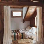 Bedroom, Wooden Floor, Bed On The Floor With Colorful Blanket, White Wall, Sloping Wooden Ceiling, White Curtain