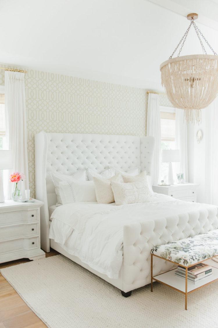bedroom, wooden floor, beige rug, white bedding, white bed platform tufted, wraparound headboard, white bedside cabinet, chandelier