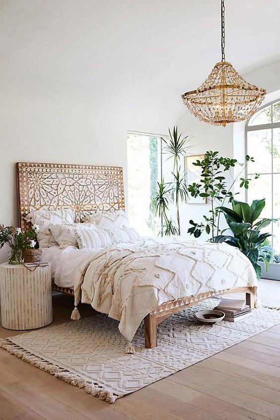bedroom, wooden floor, beige rug, white wall, white ceiling, white bedding, wooden bed platform detailed headboard, wooden chandelier, white round side table
