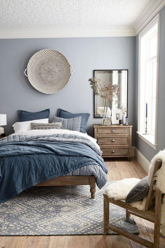 bedroom, wooden floor, blue rug, blue bedding, wooden bed platform, light blue wall, white pattern textured ceiling, wooden bedsde cabinet, mirror, wooden chair