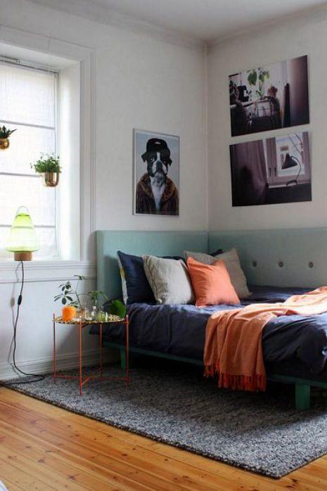 bedroom, wooden floor, grey rug, light green corner wraparound headboard, white wall, orange metal side table