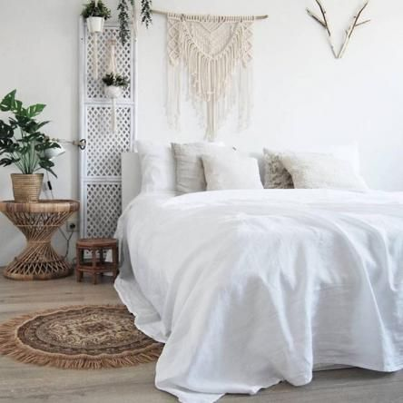 bedroom, wooden floor, white bedding, macrame, small white wooden partition, wooden rattan side table, plants