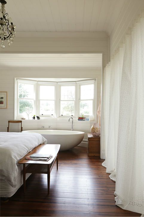bedroom, wooden floor, white wooden ceiling, white wall, alcove space with windows and bathtub, white bed, wooden bench, chandelier