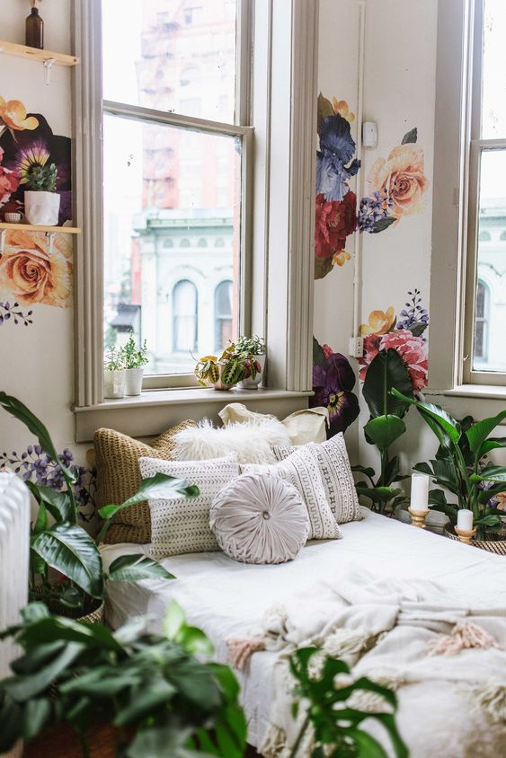 bedroom, wooden flor, plants on floor, white bedding, flowery wallpaer