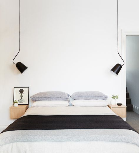 bedside hanging lights with black cover, white wall, white bedding, small floating wooden box