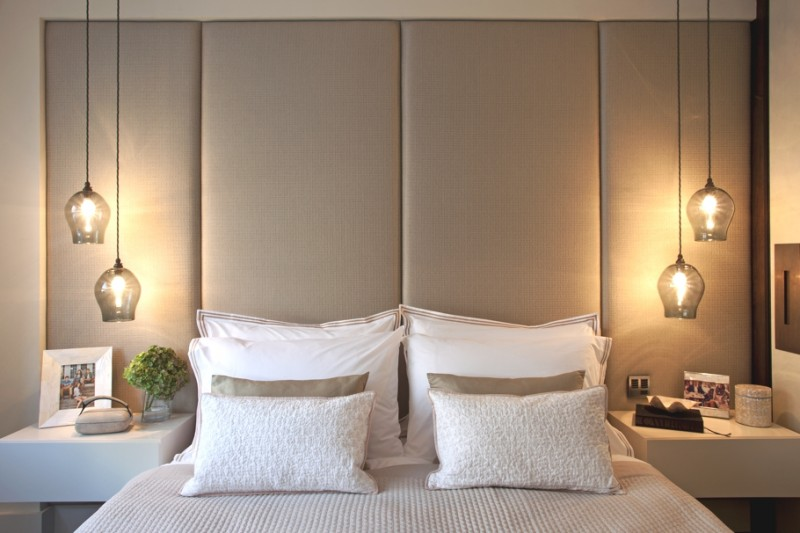 bedside hanging lights with glass cover, white floating table, white bedding pillows, beige accent wall
