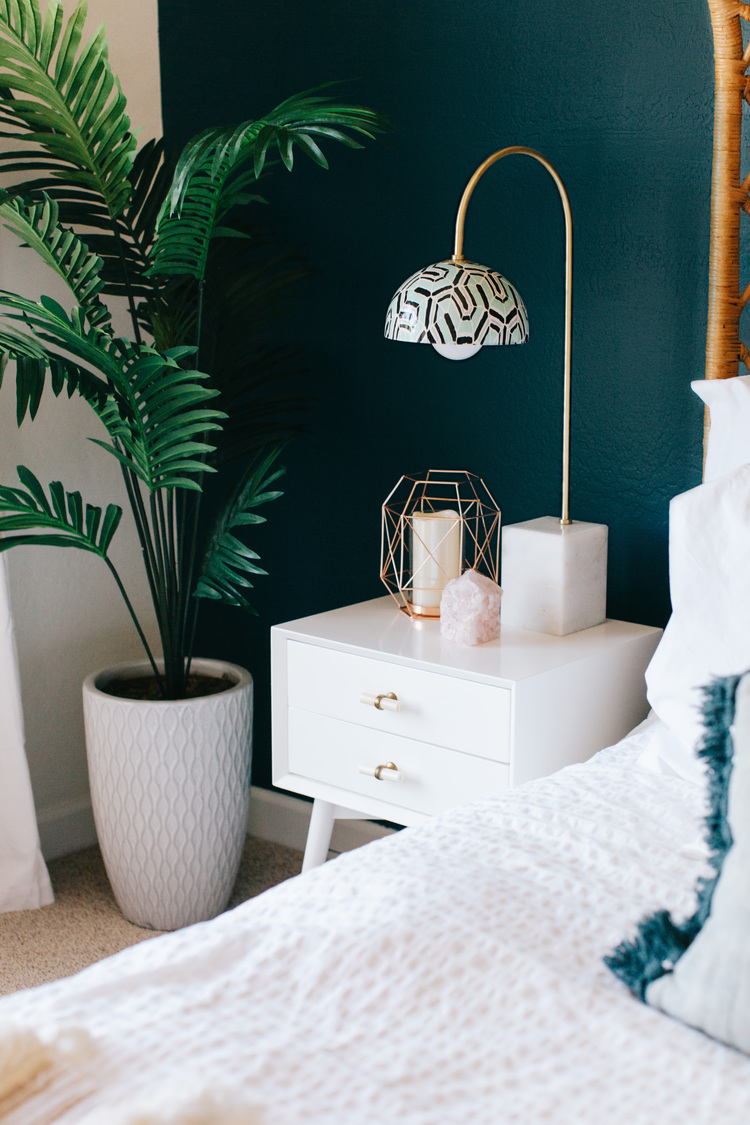bedside table, white marble base, golden brass thin body, white cover with pattern, white bedside cabinet, beige rug, white bedding, white pot with plant, green wall, white wall
