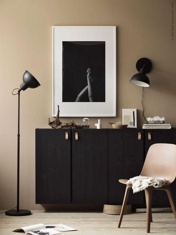 black floating cabinet, beige wall, wooden floor, black sconce, black floor lamp, wooden modern chair