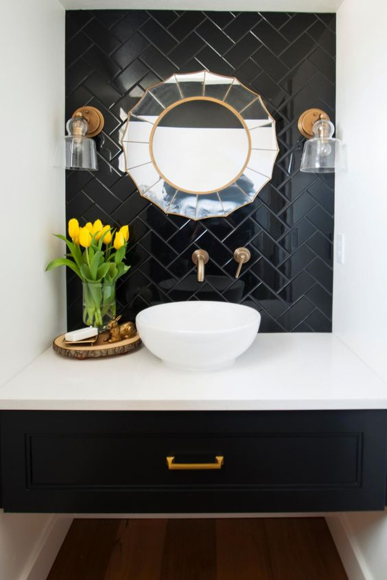 black floating vanity, white counter top, white sink, white wall, black herringbone accent wall, sun shaped mirror, glass sconces,