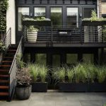 Black House, Black Staurs, Plants On Floating Shelves On The Railing, On The Wall, Vines On Stairs, Black Pots On The Ground