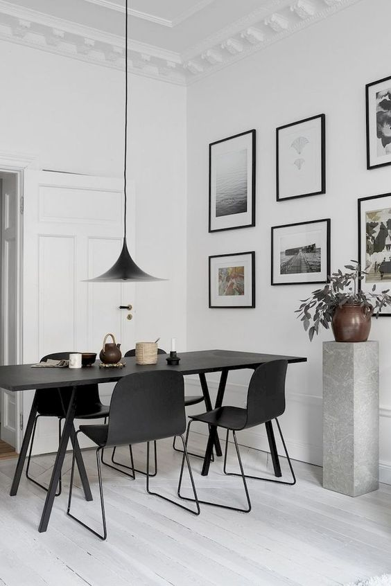 black rectangular table with black modern chairs, white floor, white wall, black pendant