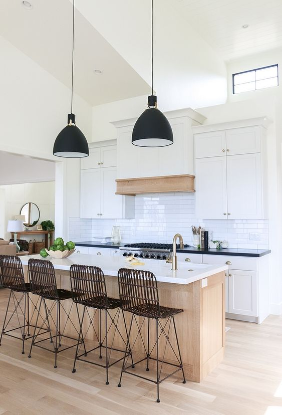 black wired bar stool on back and legs, wooden island with white top, wooden floor, white cabinet, white backsplash tiles, black cover pendants