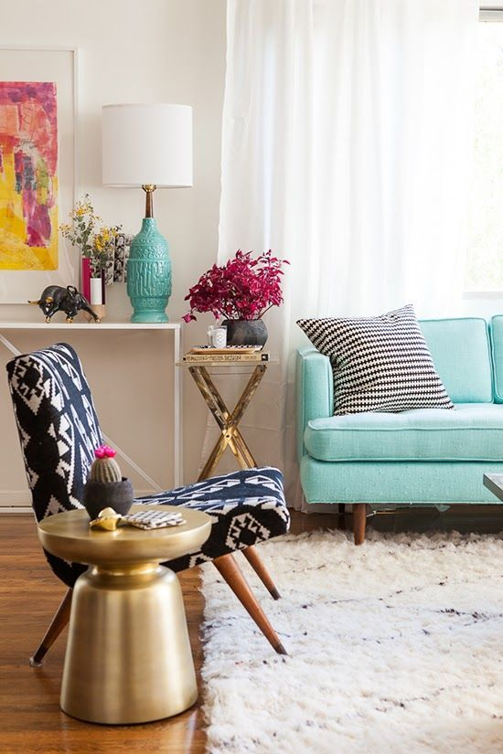 blue ethnic patterned chair, white rug, golden side table, tosca sofa, white wall, white console table, table lamp