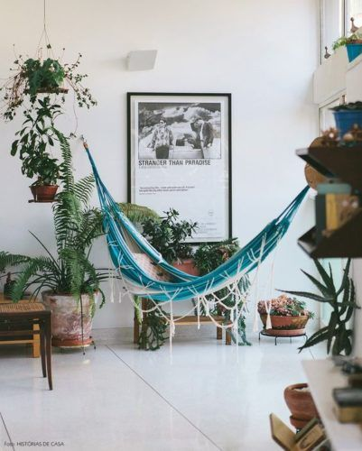 blue hammock in the living room, white floor tiles, white wall, plants on pots, wooden coffee table
