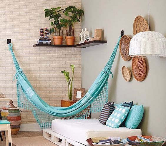 blue hammock on living room, wooden floor, platfrom, cushion, rug, grey wall, open brick accent wall, corner floating wall