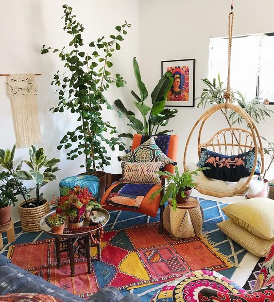 bohemian living room, blue rug, colorful rug, orang lounge chair with colorful pillows and blanket, blue ottoman, white wall, rattan swinging chair, tray coffee table, plants,