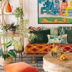 Bohemian Living Room, Grey Rug, Low Round Wooden Table, Wooden Bench With Orange Cushion, Green Pillows, White Wall, Rattan Plants Shelves, Orange Pillow, Plants Pot