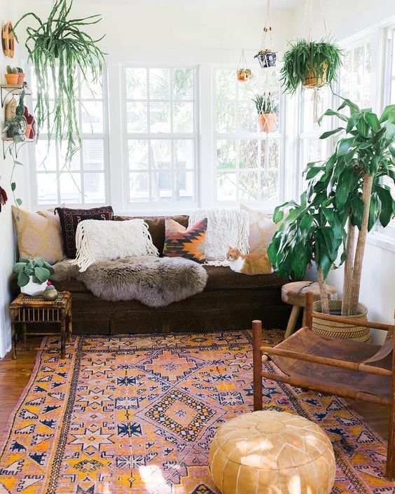 bohemian living room, wooden floor, orange rug, brown sofa, earthy colored pillows, white wall, white ceiling, plants