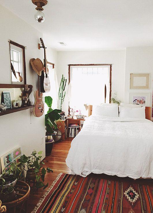 boho bedroom, wooden floor, warm rug, white bedding, white wall, white ceiling, plants on the floor, foating shelves, guitar