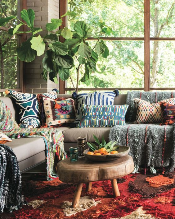 boho living room, grey sofa, colorful pillows and blankets, low wooden coffee table, red orange rug