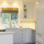 Cabinets To Ceiling Glass Windows Rattan Shade Backsplash Recessed Lighting White Cabinets White Drawers Dark Wooden Floor Stovetop