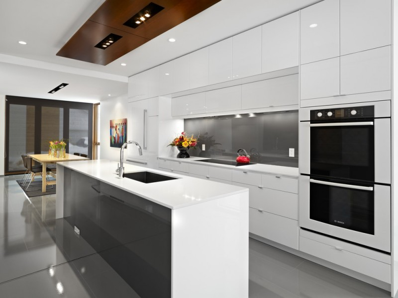 cabinets to ceiling grey glossy backsplash stovetop built in appliances sink faucet island drawers refrigerator wooden dining table vent chairs