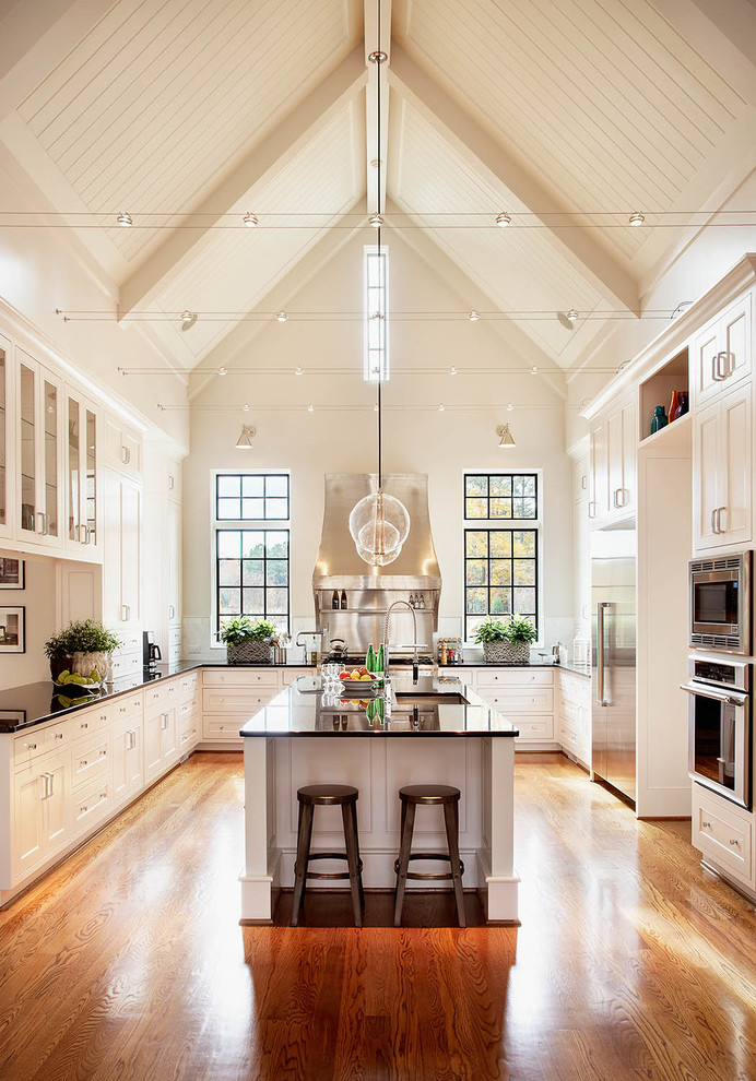 cabinets to ceiling oak flooring island stools glass pendant lamps grid glass windows black countertops sink faucet built in kitchen appliances