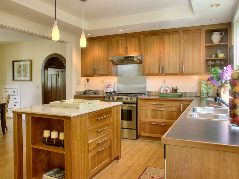 cabinets to ceiling wooden cherry cabinet range hood pendant lamps wooden island grey countertops stovetop shelves double sink faucet drawes windows