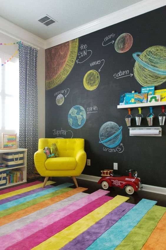 children's room, colorful stripes rug, black wall with planets drawing, grey curtain, yellow chair, white shelves, white floating shelves