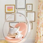 Clear Acrylic Round Bedroom Swinging Hanging Chair With Orange Cushions, Dolls, White Rug, White Wall, Grey Floor