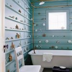 Coastal Bathroom, Blue Wooden Wall With Shelves The Entire Wall, Shells And Starfishes On The Entire Wall, White Tub, White Chairs, Black Stool