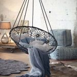 Dark Blue Hanging Chair In Pattern Woven Chair With Pillows And Blaket, Wooden Floor, Ottoman, Table Lamp