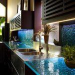 Dark Kitchen, Dark Brown Cabinet, Dark Wooden Shelves With Wooden Bars Cover, Blue Watery Countertop And Backsplash