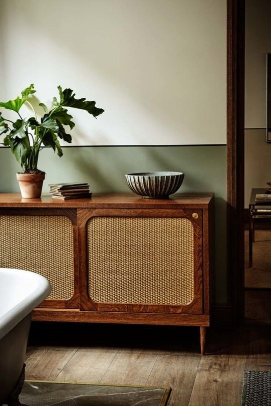 dark wooden cabinet with rattan slide door, wooden floor, green off white wall